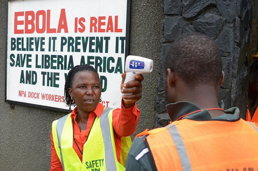 A security agent controls the temperature of a woman at the entrance of the port of Monrovia on Aug 29, 2014. -- PHOTO: AFP