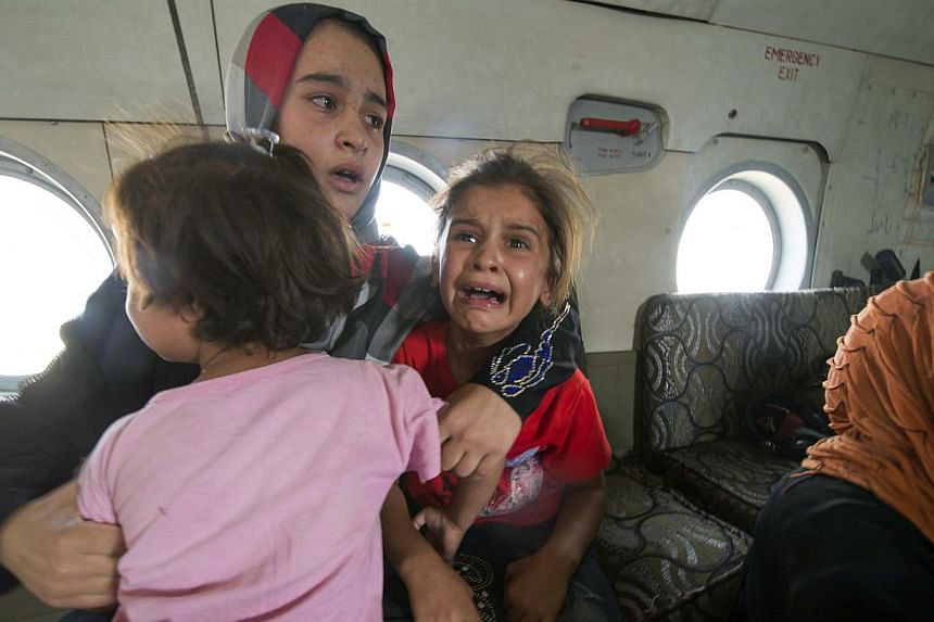 A woman and children react in a military helicopter after being evacuated by Iraqi forces from Amerli, north of Baghdad on Aug 29, 2014. -- PHOTO: REUTERS