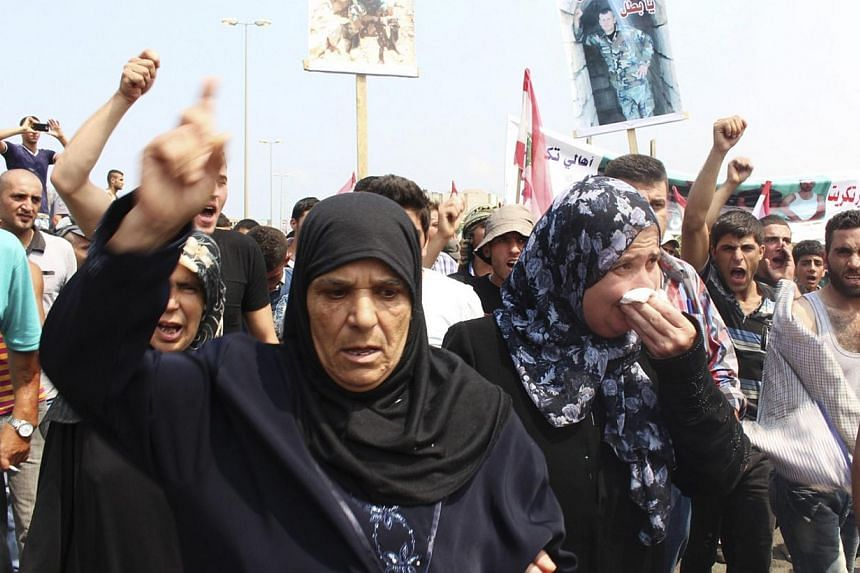 Relatives of Lebanese soldiers captured by Islamist militants in Arsal react during a protest demanding their release and pressuring the government to act, as they block a main road linking Tripoli to Halba, in al-Mhmara town, northern Lebanon on Aug