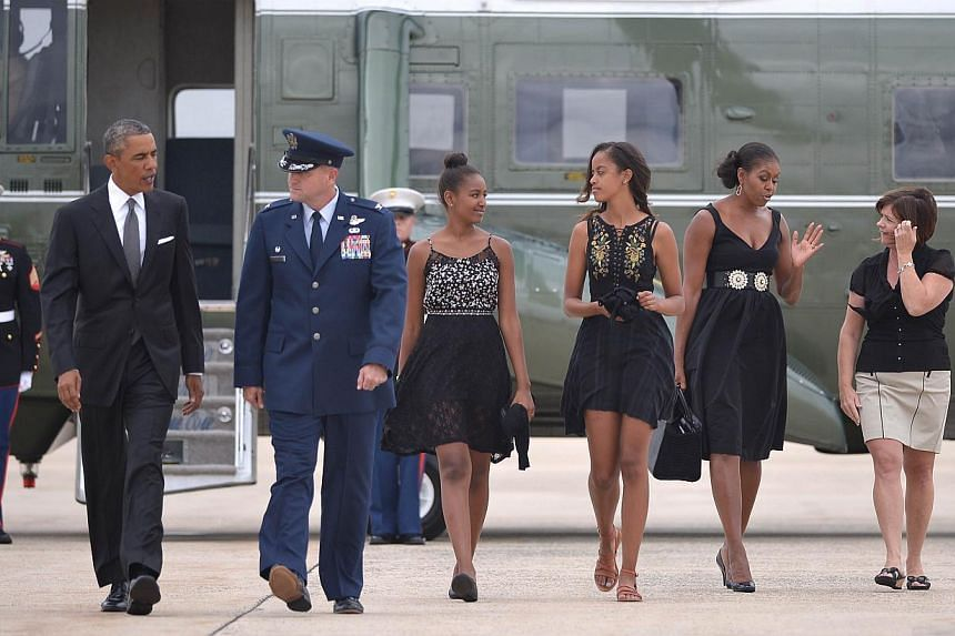 US President Barack Obama (left) and First Lady Michelle Obama (second from right) with daughters Malia (centre right) and Sasha make their way to board Air Force One before departing from Andrews Air Force Base in Maryland on August 30, 2014. Obama