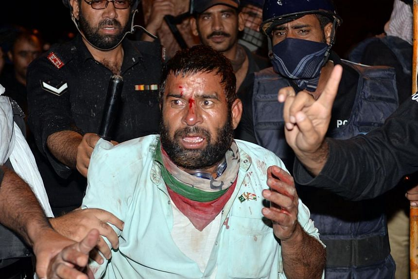 Pakistani policemen arrest an injured supporter of Canadian cleric Tahir ul Qadri following clashes with security forces near the prime minister's residence in Islamabad on Aug 31, 2014. -- PHOTO: AFP