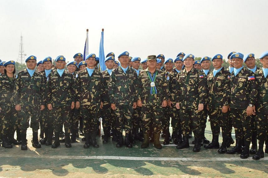 A handout photo taken in October 2013 and released by Philippine Armed Forces public affairs office on August 29, 2014 shows officers and men of the 7th Philippine peacekeeping force bound for the Golan Heights posing for photos during their send-off