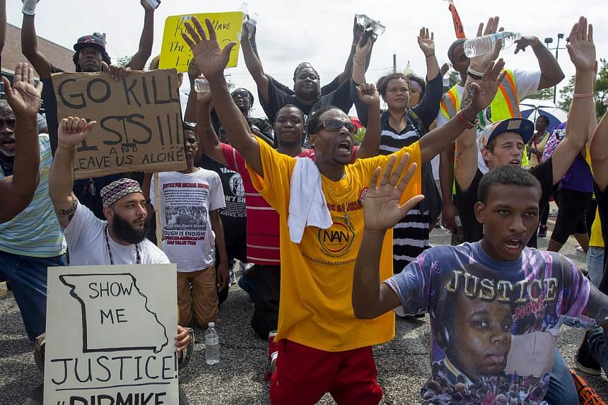 Protesters sit down in the street outside the police department during a protest over the killing of Michael Brown in Ferguson, Missouri on Aug 30, 2014. -- PHOTO: AFP