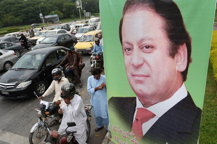 Pakistani commuters wait at traffic lights alongside a poster of Prime Minister Nawaz Sharif on a highway in Islamabad on August 25, 2014.Sharif on Saturday dismissed a political crisis triggered by protests aimed at unseating his government as