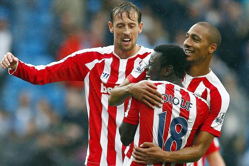 Stoke City's Peter Crouch (left), Mame Diouf and Steven N'Zonzi (right) celebrate defeating Manchester City in their English Premier League soccer match at the Etihad stadium in Manchester, northern England on Aug 30, 2014. -- PHOTO: REUTERS