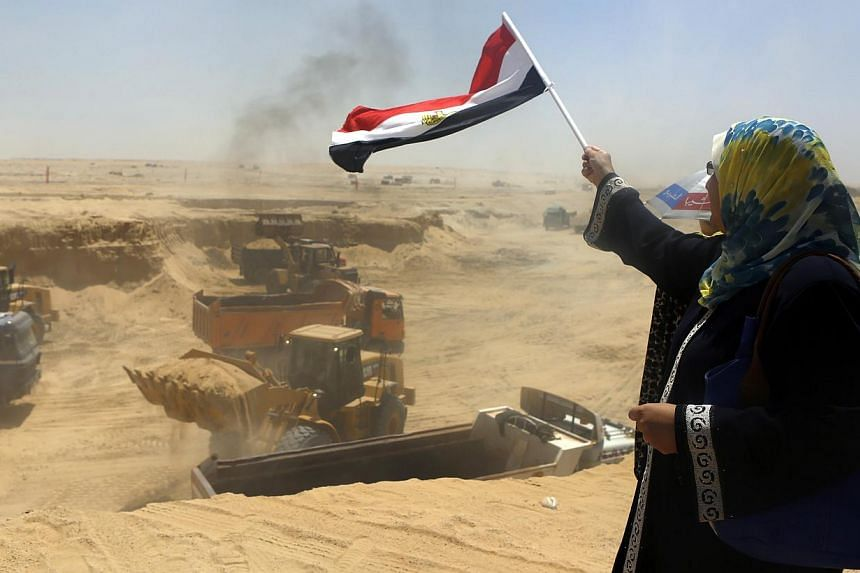 An Egyptian woman waves a national flag as machinery is driven during an upgrading project on the Suez Canal, in Ismailia port city, north-east of Cairo August 12, 2014. The project includes the development of 76,000 sq km around the canal into