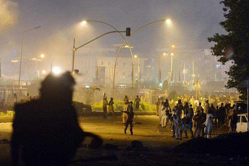 Pakistani opposition protesters throw stones towards the police following clashes with security forces near the Prime Minister's residence in Islamabad on August 30, 2014. Police in Pakistan's capital Islamabad fired tear gas on anti-government prote