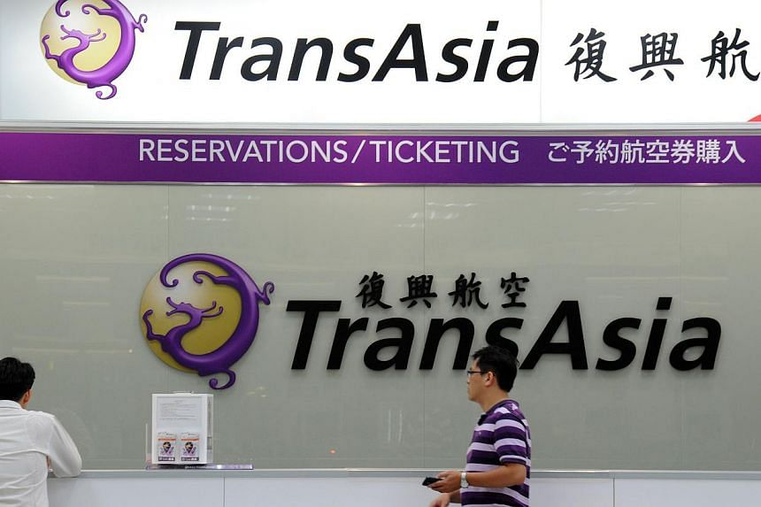 Local journalists wait in front of a TransAsia reservations desk at the Sungshan airport in Taipei on July 23, 2014. -- PHOTO: AFP