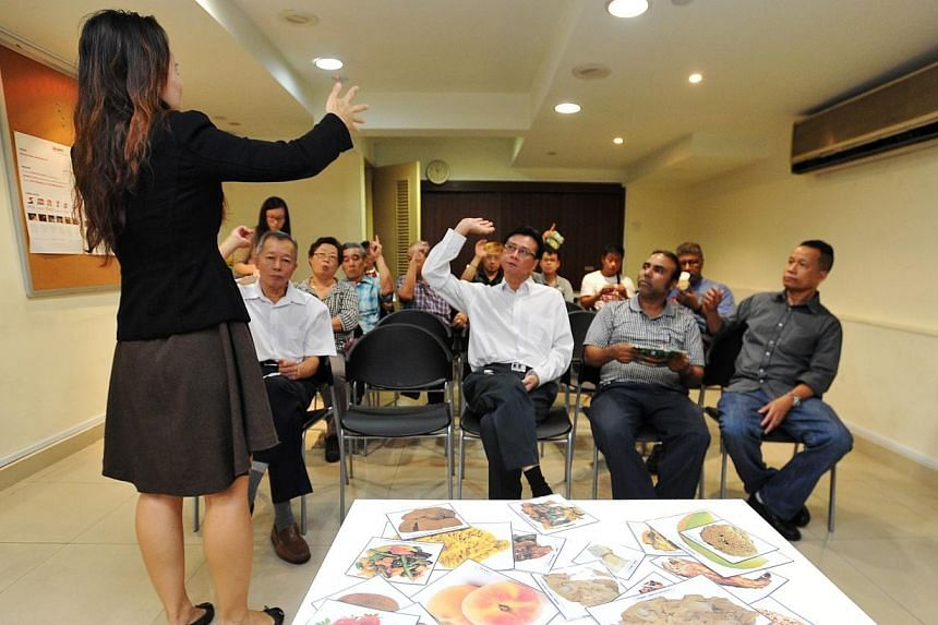 Health Promotion Board trainer Elaine Wong conducting a Healthy Tasty Food Workshop for SMRT taxi drivers at the SMRT Taxis Customer Service Centre on Monday, Sept 1, 2014.-- ST PHOTO: LIM YAOHUI