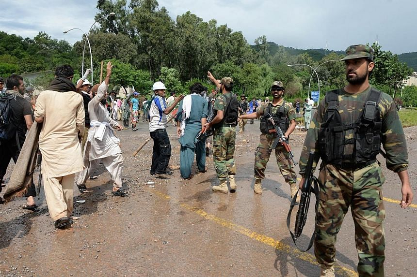 Pakistani army soliders disperse protestors after clashes with anti-government demonstrators and police near the prime minister's residence in Islamabad on Sept 1, 2014.Pakistani soldiers and paramilitary forces entered the headquarters of the