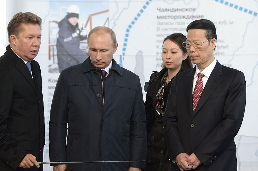 """Russia's gas giant Gazprom CEO, Alexei Miller (left), Russian President Vladimir Putin (2nd from left) and Vice Premier of the People's Republic of China Zhang Gaoli (right) attend the ceremony marking the welding of the first link of """"The Power of S"""