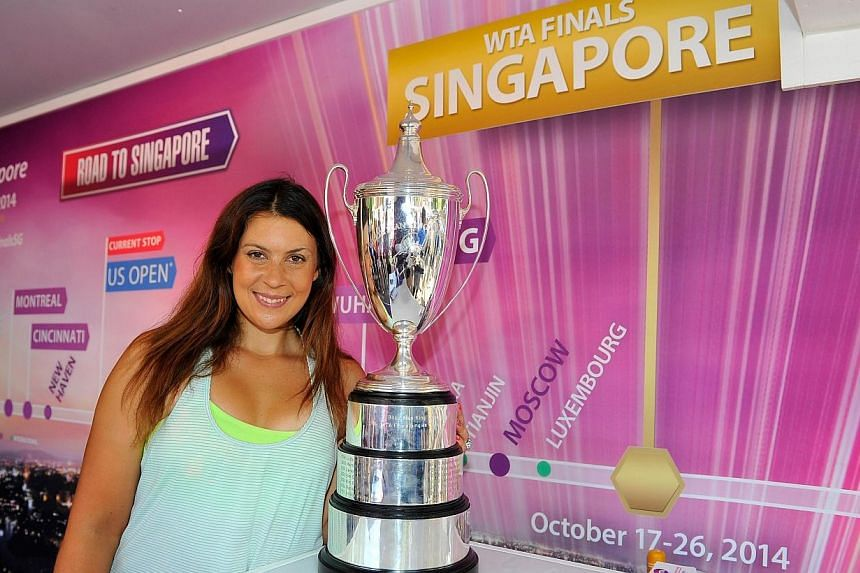 Marion Bartoli poses with the WTA Billie Jean King Trophy on Day Three of the 2014 US Open at the USTA Billie Jean King National Tennis Center on Aug 27, 2014 in the Flushing neighborhood of the Queens borough of New York City. Bartoli will play in t