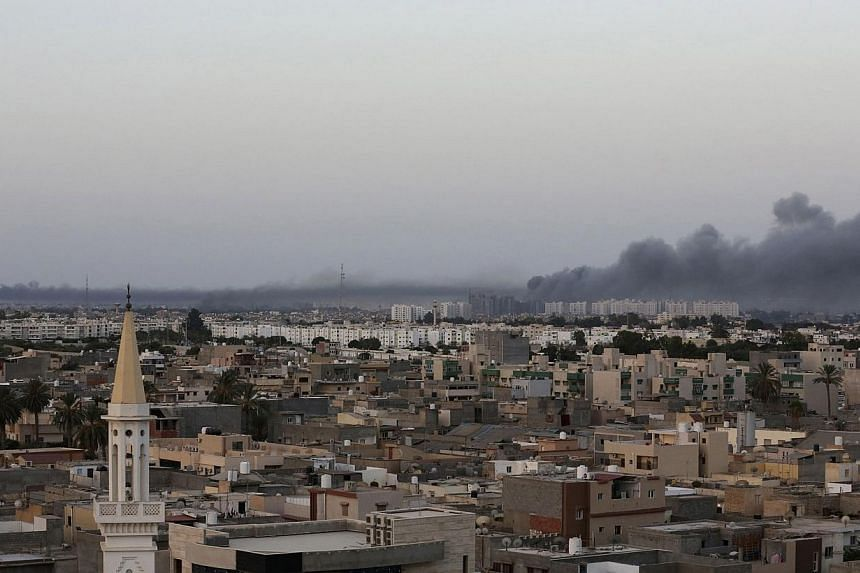Plumes of black smoke (right) is seen after war planes struck Misrata positions in Tripoli in an attack claimed by renegade general Khalifa Haftar, on Aug 23, 2014.Libya's government said it has lost control of most ministries and state institu