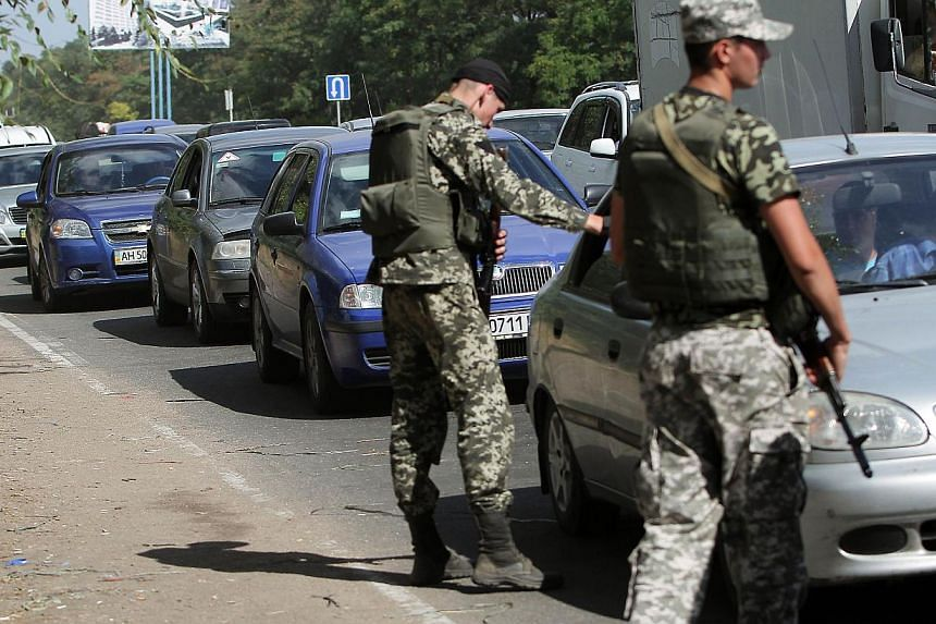 Ukranian troops stopping cars at a checkpoint in Mariupol, in the Donetsk region, last Saturday. Geo-political uncertainties, coupled with questions over emerging markets and the many local companies missing earnings forecasts, could bring trading or