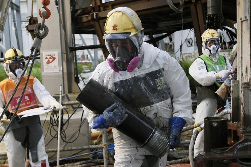 Workers conduct operations to construct an underground ice wall at Tokyo Electric Power Co.'s (Tepco) tsunami-crippled Fukushima Daiichi nuclear power plant in Fukushima Prefecture on July 9, 2014.The governor of disaster-struck Fukushima agree
