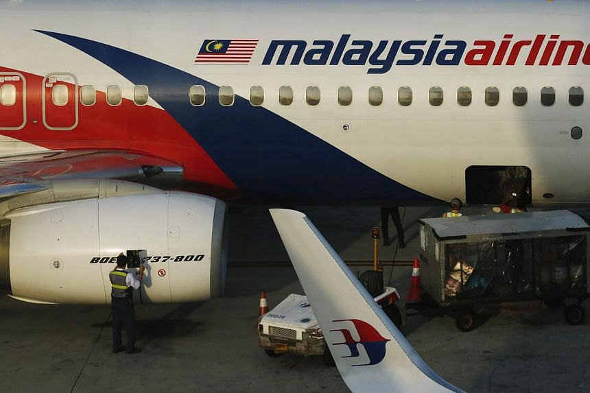 A member of ground crew works on a Malaysia Airlines Boeing 737-800 airplane on the runway at Kuala Lumpur International Airport in Sepang. -- PHOTO: REUTERS