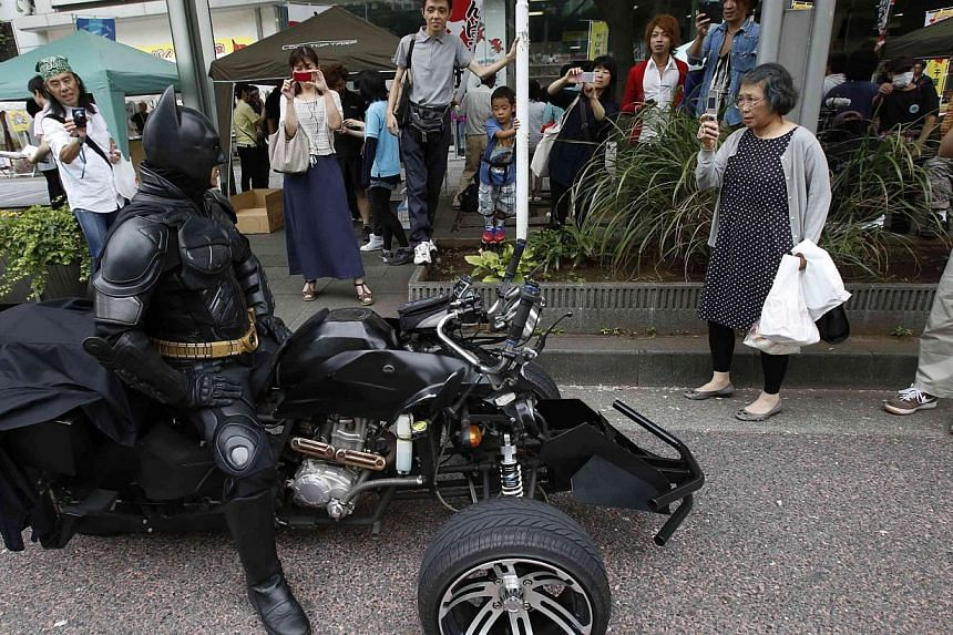 "Chibatman posing for pictures on his ""Chibatpod"" in Chiba, east of Tokyo, on Aug 31, 2014.-- PHOTO: REUTERS"