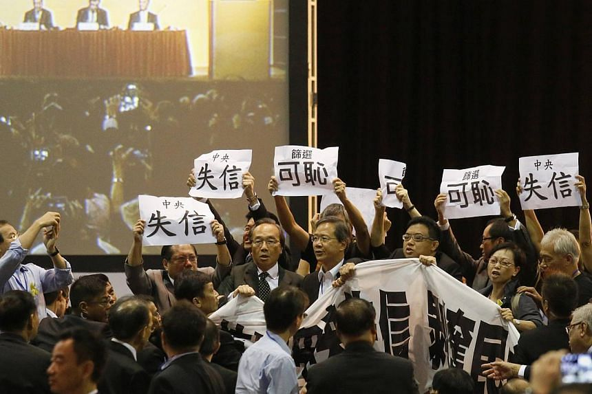 Pro-democracy lawmakers hold up a banner and signs during a protest as Li Fei (seen on screen), deputy general secretary of the National People's Congress (NPC) standing committee, speaks during a briefing session in Hong Kong September 1, 2014. Pro-