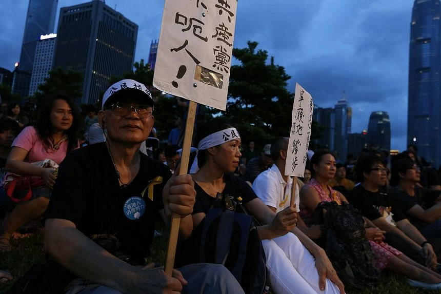 """A pro-democracy protester carries a placard which reads """"Communist Party, you lie!"""" as he sits with other protesters during a campaign to kick off the Occupy Central civil disobedience event in front of the financial Central district in Hong Kong on"""