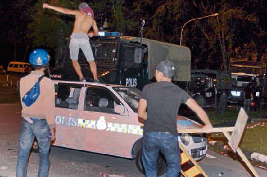 Rioters damaged police vehicles during the riot. -- PHOTO: NSTP