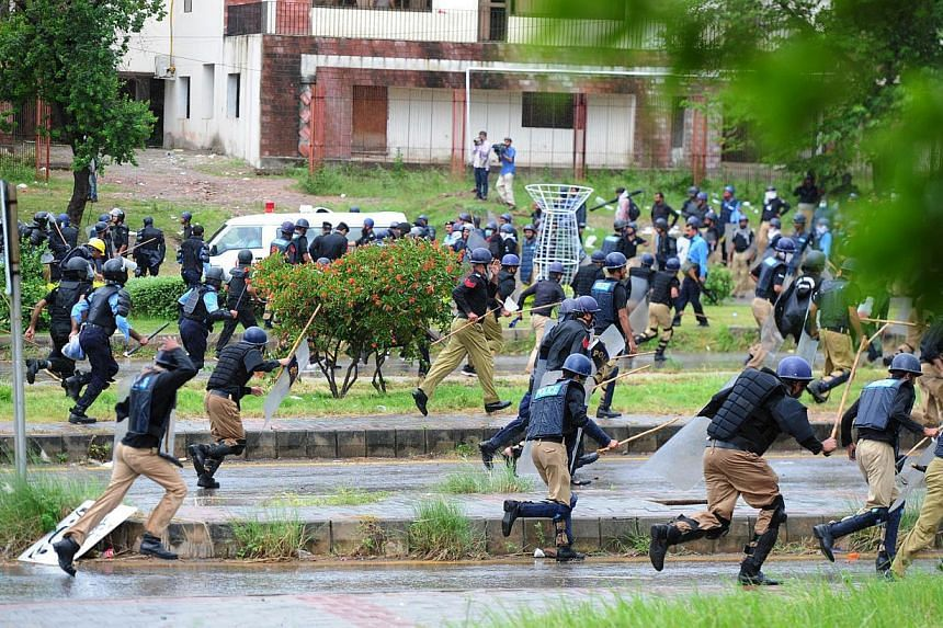 Pakistani police run from opposition protesters during clashes near the prime minister's residence in Islamabad on Sept 1, 2014. -- PHOTO: AFP