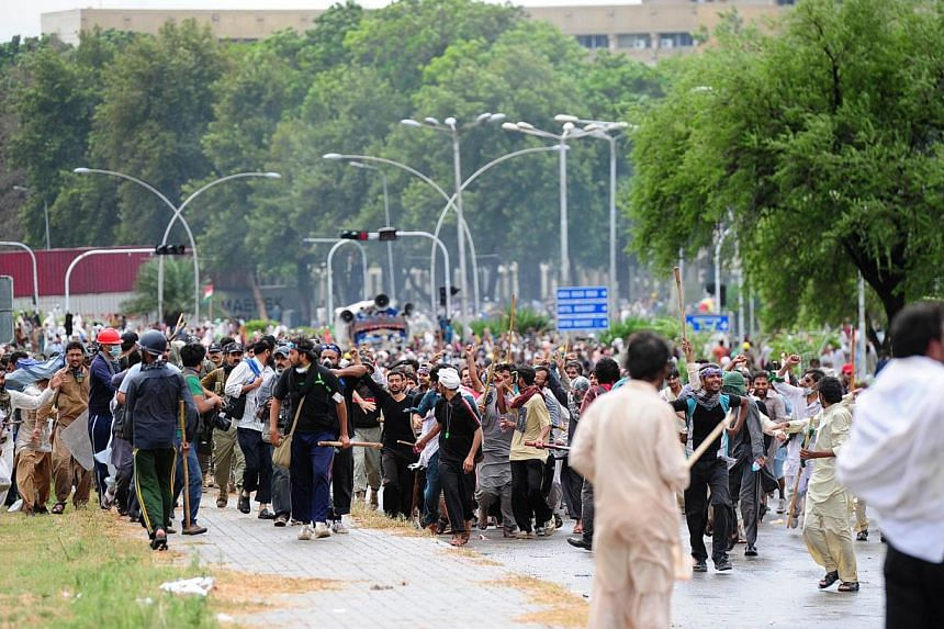 Pakistani opposition protesters gather during a clash with police near the prime minister's residence in Islamabad on Sept 1, 2014. -- PHOTO: AFP