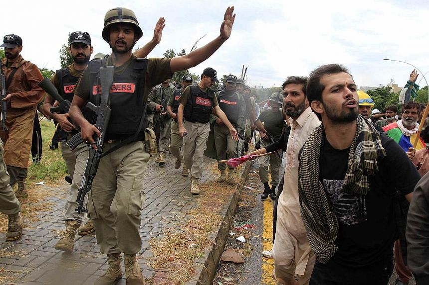 Soldiers from the Pakistan Rangers stop supporters of Tahir ul-Qadri, Sufi cleric and leader of political party Pakistan Awami Tehreek (PAT), during Revolution March towards the prime minister's house in Islamabad. -- PHOTO: REUTERS