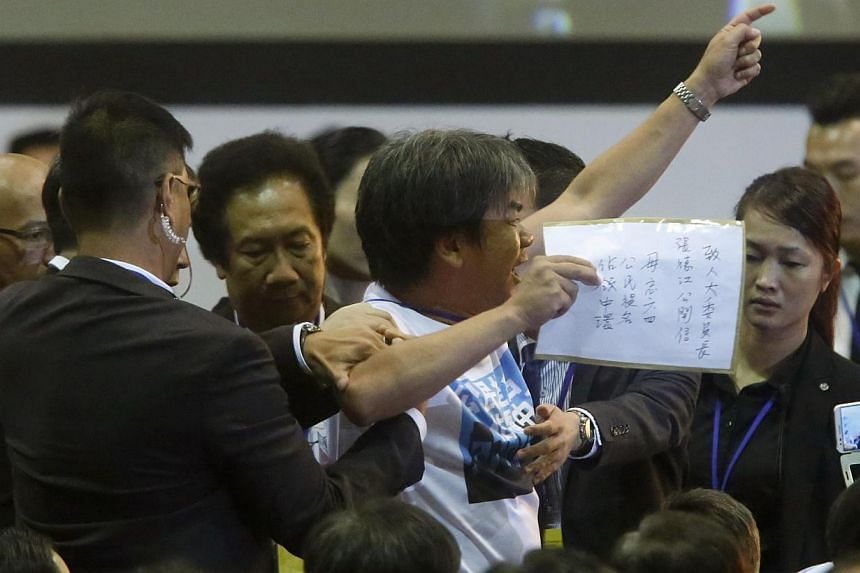 Pro-democracy lawmaker Leung Kwok-hung is blocked by security guards as he protests against Li Fei (not pictured), deputy general secretary of the National People's Congress (NPC) standing committee, as Li speaks on the podium during a briefing sessi