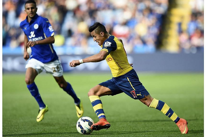 Arsenal's Alexis Sanchez (right) runs with the ball during their English Premier League soccer match against Leicester City at the King Power Stadium in Leicester, northern England on Aug 31, 2014. -- PHOTO: REUTERS