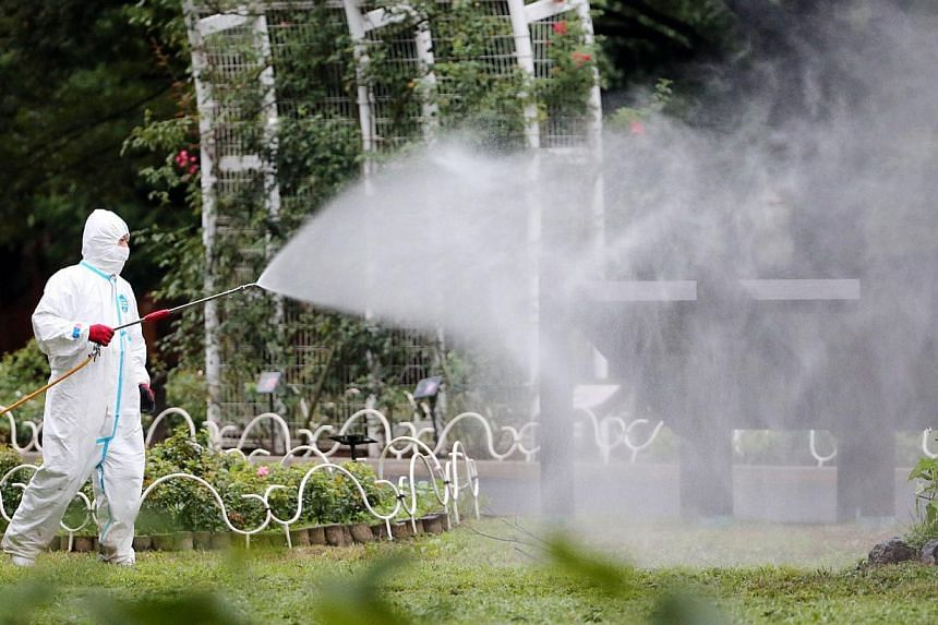 This picture taken on August 28, 2014 shows a worker spraying insecticide at the Yoyogi park, one of the largest open spaces in central Tokyo, believed to be the source of the mosquito-borne dengue fever. -- PHOTO: AFP