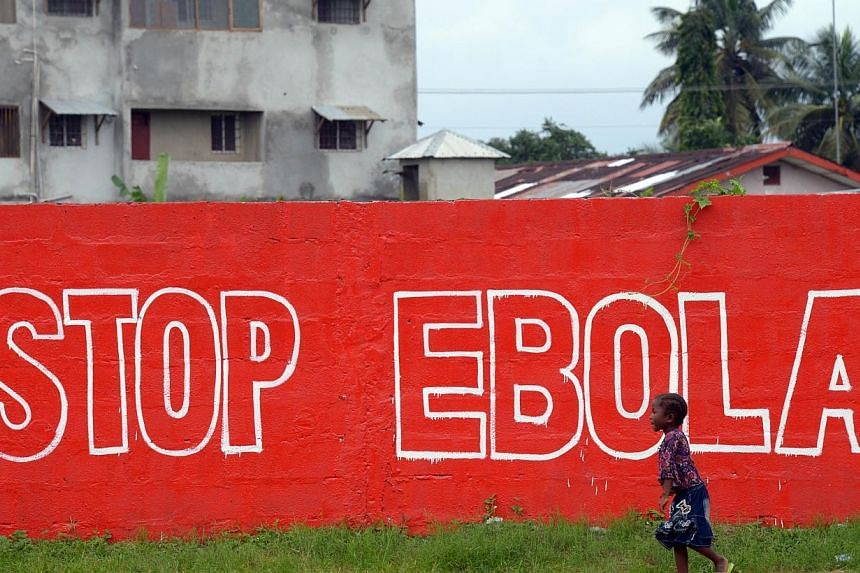 A girl walks past a slogan painted on a wall in Monrovia on Aug 31, 2014.Japanese researchers said Tuesday they had developed a new method to detect the presence of the Ebola virus in 30 minutes, with technology that could allow doctors to quic