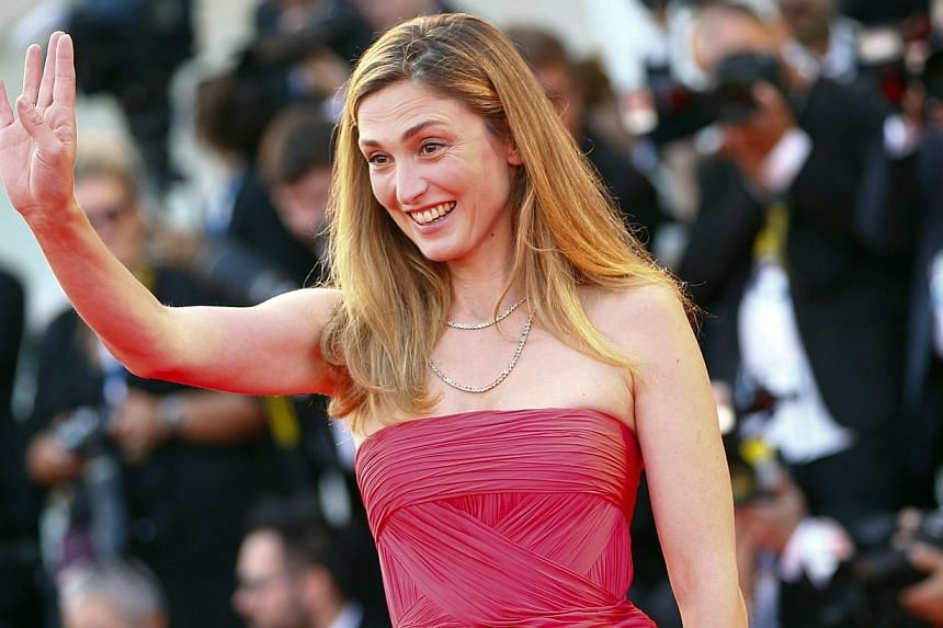 Actress Julie Gayet gestures as she arrives on the red carpet for the opening ceremony of the 71st Venice Film Festival in Venice on Aug 27, 2014. French actress Julie Gayet, whose affair with President Francois Hollande made headlines worldwide