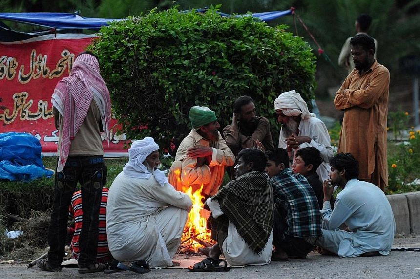 Pakistani supporters of cricketer-turned politician Imran Khan and Canadian cleric Tahir ul Qadri warm themselves around fire during an anti-government protest near the prime minister's residence in Islamabad on Sep 2, 2014.Pakistani Prime Mini