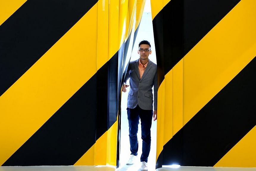 Artist Michael Lee uses the black and yellow diagonal stripes of barricade tapes to signal a danger zone in Diagonals. -- ST PHOTO: JAMIE KOH