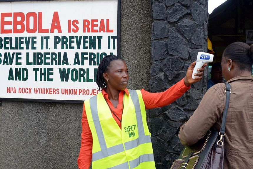 A security agent controls the temperature of a woman at the entrance of the port of Monrovia on Aug 29, 2014. An outbreak of the Ebola virus in the Democratic Republic of Congo has killed 31 people and the epidemic remains contained within the c