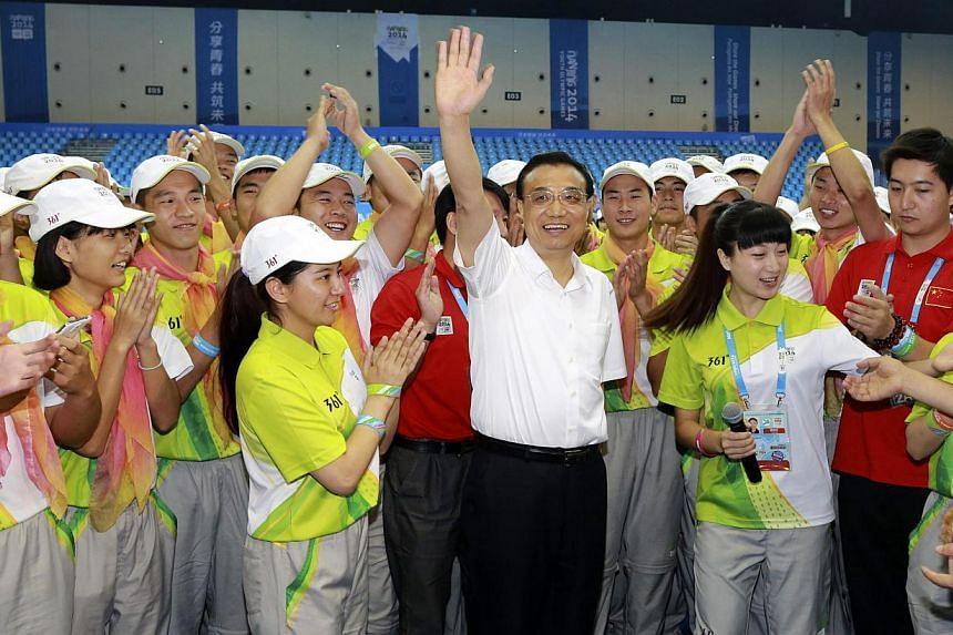 Chinese Premier Li Keqiang (centre) waves as he meets with volunteers of the 2014 Nanjing Youth Olympic Games in Nanjing, Jiangsu province on Aug 28, 2014. -- PHOTO: REUTERS