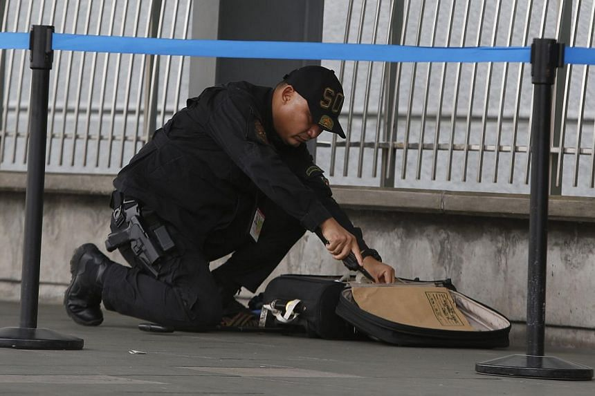 A member of the Philippine National Police's Explosive Ordinance Disposal unit examines abandoned luggage found at the entrance of Terminal 3 of the Ninoy Aquino International airport in Pasay City, Metro Manila on Sept 1, 2014. -- PHOTO: REUTERS