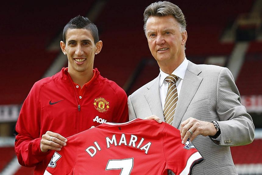 Manchester United's new signing Angel Di Maria (left) poses for a photograph with his shirt and with manager Louis van Gaal at Old Trafford in Manchester, northern England on Aug 28, 2014. -- PHOTO: REUTERS
