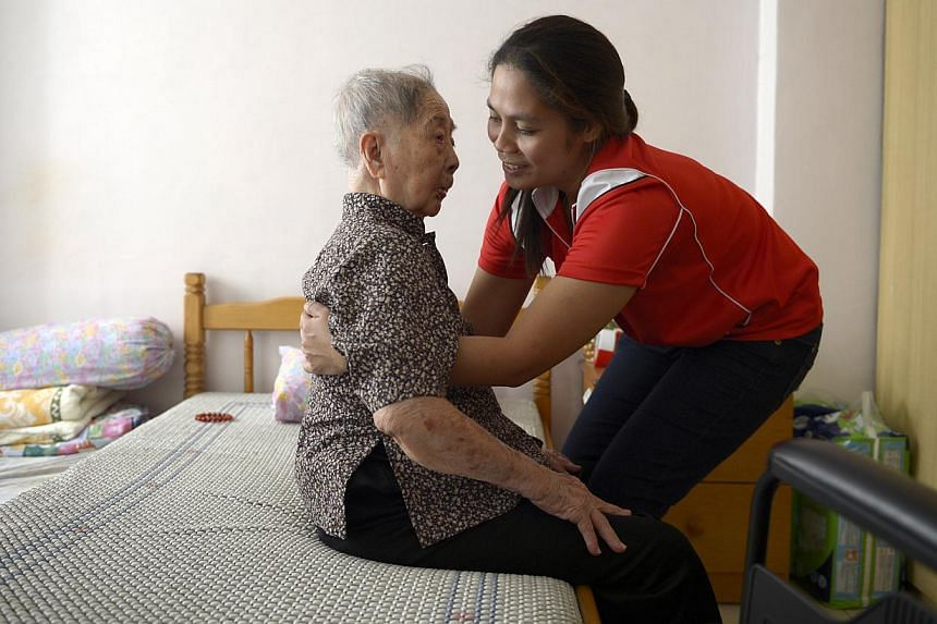 Ms Jenny Exconde (right), a care worker, is trained in a range of services to provide for all the needs of Madam Lim Yim Tee at home. -- PHOTO: ST FILE