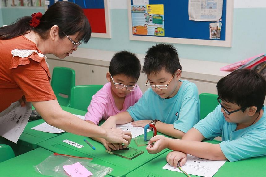 Primary school pupils with a volunteer teacher at a CDAC tuition centre at Sengkang Primary on Aug 31, 2014. -- PHOTO: ZAOBAO