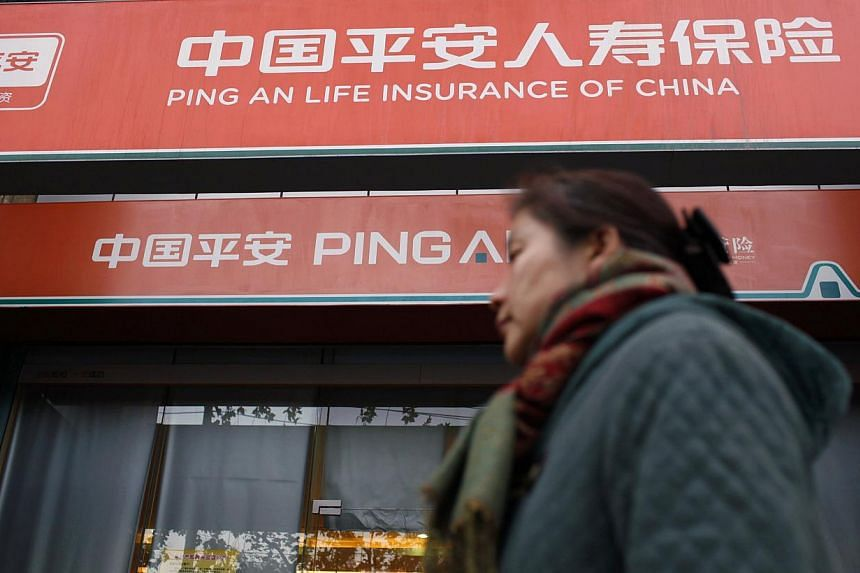 A woman walks past a Ping An Insurance building in Shanghai in this December 6, 2012 file photo. Ping An is among 23 Chinese insurance firms said by authorities on Tuesday to have colluded to fix fees. The companies were slapped with a total of 110 m