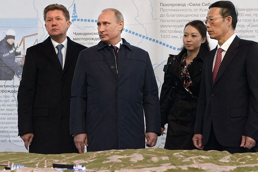 """Russian gas giant Gazprom CEO Alexei Miller (left), Russian President Vladimir Putin (second from left) and Chinese Vice-Premier Zhang Gaoli (right) attend the ceremony marking the welding of the first link of """"The Power of Siberia"""" main gas pipeline"""