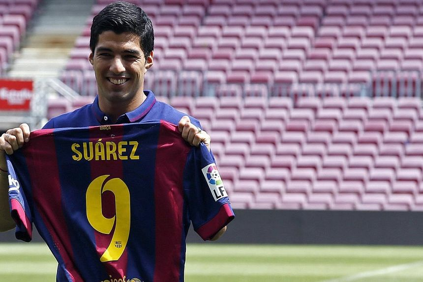 FC Barcelona's Luis Suarez holds up his jersey during his presentation at the Nou Camp stadium in Barcelona on Aug 19, 2014. -- PHOTO: REUTERS