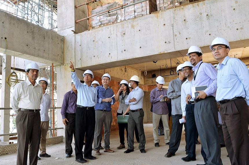 Minister-in-Charge of Muslim AffairsDr Yaacob Ibrahim (middle, pointing upwards) visiting the Al-Ansar Mosque work site in Bedok on Sept 2, 2014 to view the latest construction work being done. -- PHOTO: BERITA HARIAN