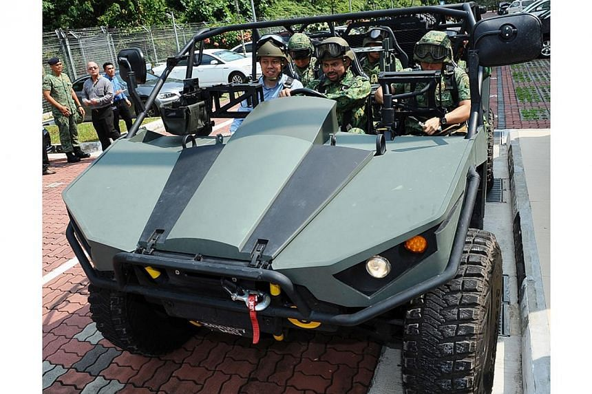 Brunei's Crown Prince Al-Muhtadee Billah, accompanied by Mr Chan, drives an upgraded Light Strike Vehicle (LSV) Mark-II. -- PHOTO: MINDEF