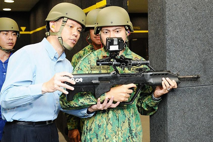 Second Minister for Defence Chan Chun Sing (left) speaks to Brunei's Crown Prince Al-Muhtadee Billah (right) as he prepares to fire the SAR-21. -- PHOTO: MINDEF