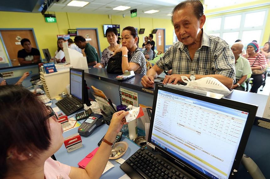 84-year-old Mr Liang Ming Chee (right) uses his Pioneer Generation card at the payment counter of Bedok Polyclinic after consultation. -- ST PHOTO: NEO XIAOBIN