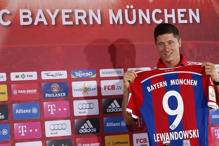 New Bayern Munich soccer player, Polish striker Robert Lewandowski, presents his new jersey during a news conference at Bayern Munich's headquarters in Munich on July 9, 2014. -- PHOTO: REUTERS