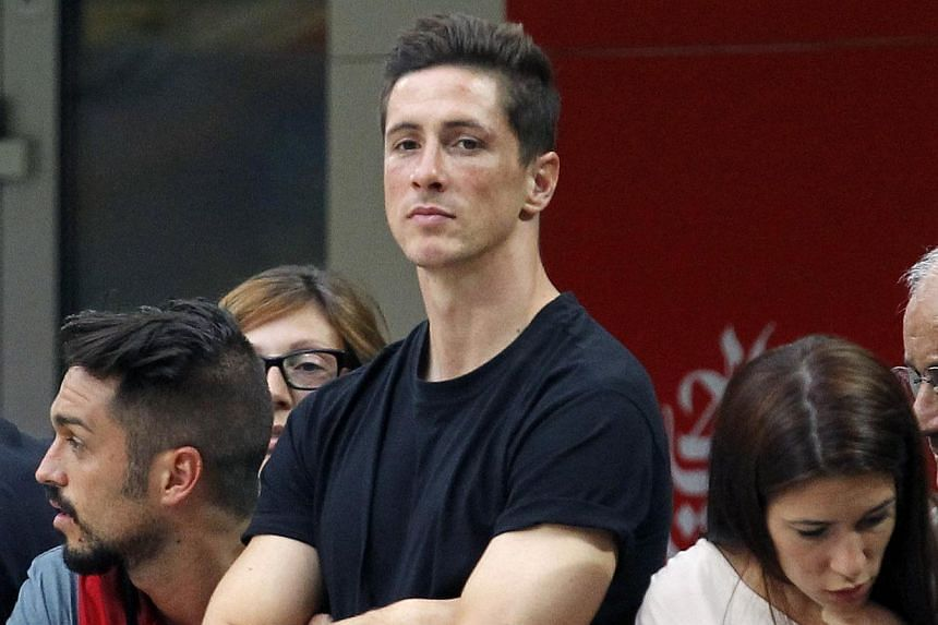 AC Milan's newly signed player Fernando Torres (centre) watches their Italian Serie A soccer match against Lazio at the San Siro stadium in Milan on Aug 31, 2014. -- PHOTO: REUTERS