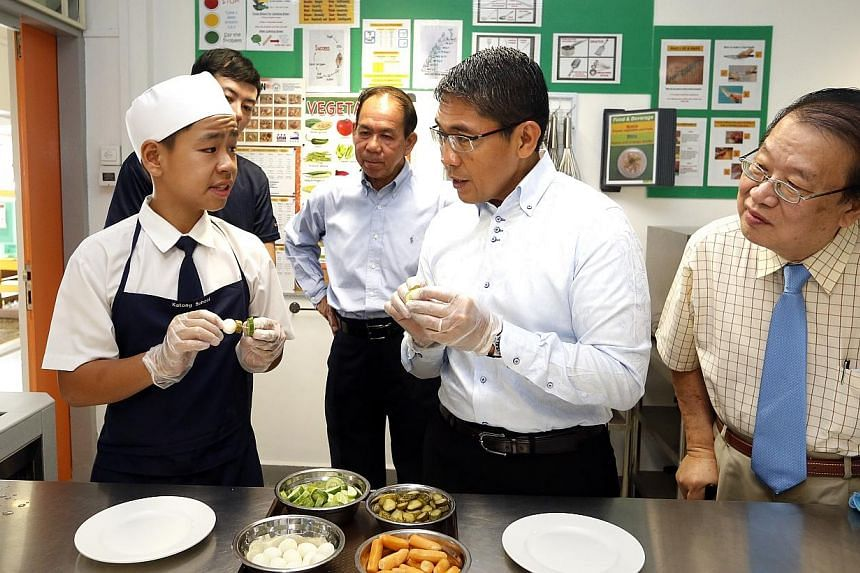 Dr Mohd Maliki Osman, Mayor of South East District and Minister of State for Ministry of Defence and National Development (centre) speaking to student Sim Yong Meng, 14 (left) and learning the process of preparing food. -- ST PHOTO: CHEW SE